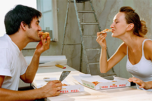 Man and woman eating pizza together