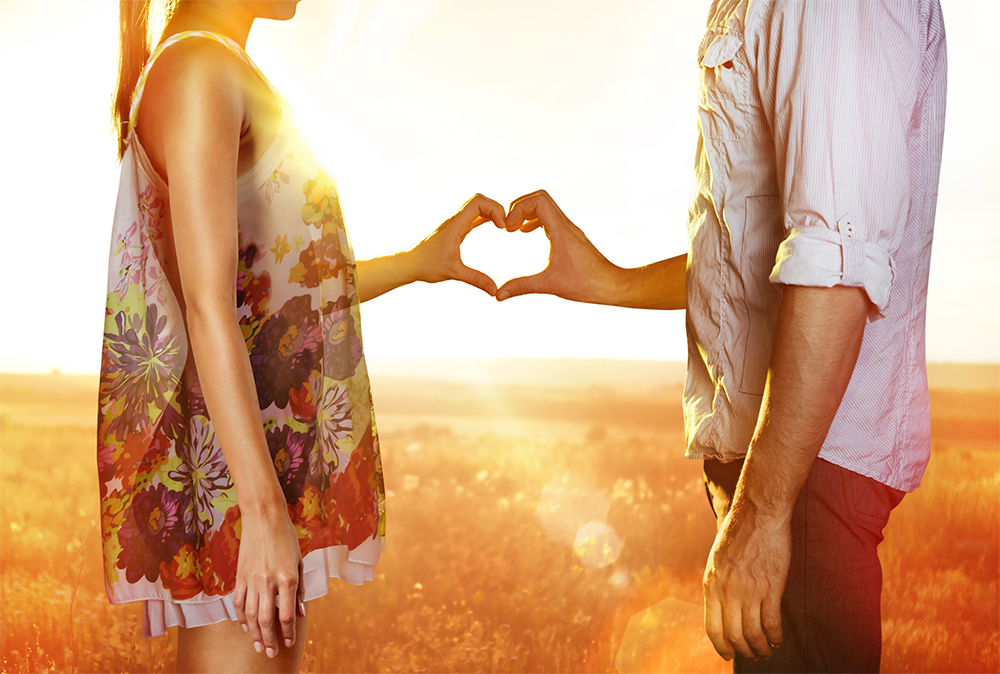 Couple in a field making a heart with their hands.