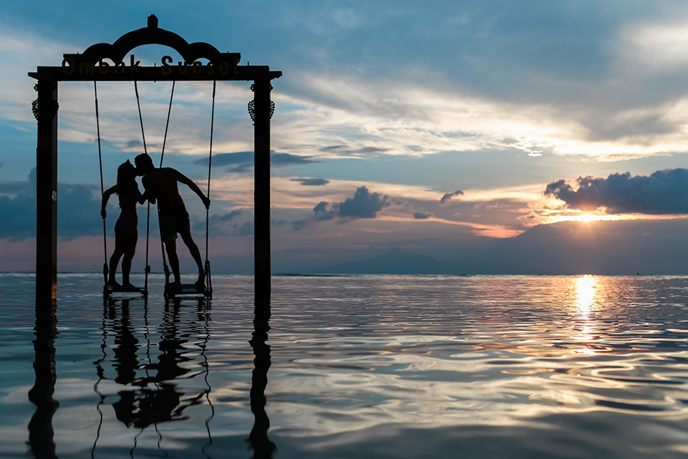 Couple kissing on swing in the ocean.