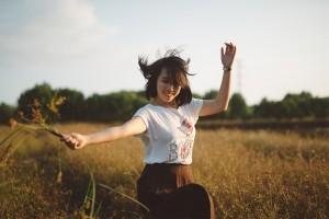 Girl spinning in field.