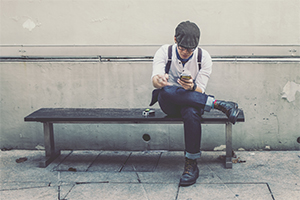 Man sitting on bench looking down at phone.