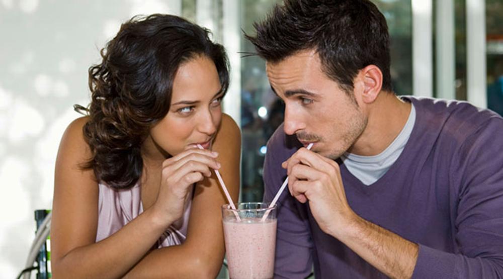 Man and woman sharing a milkshake