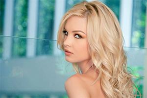 Blonde woman looking over her bare shoulder.