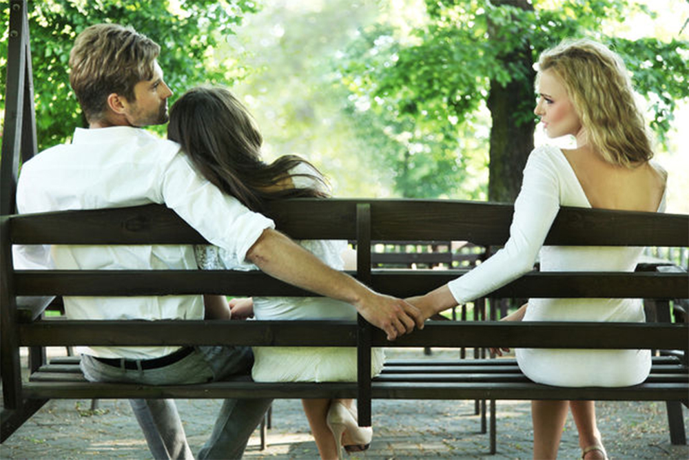 Couple on park bench, man secretly holding another woman's hand.