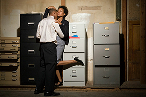 Coworkers kissing by filing cabinets.