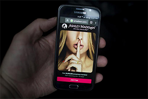 Man's hand holding phone with the Ashley Madison site on the screen.