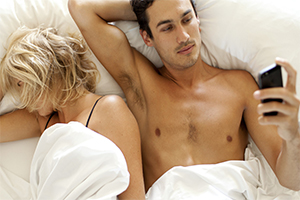 Couple in bed, woman sleeping, man on his phone.
