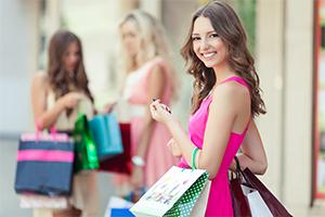 Woman carrying handful of shopping bags.
