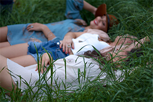 Three women laying in a grassy field together.