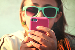 Girl wearing sunglasses texting on her pink phone