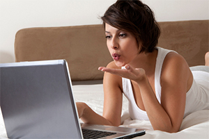 Woman laying on bed blowing kiss to computer screen