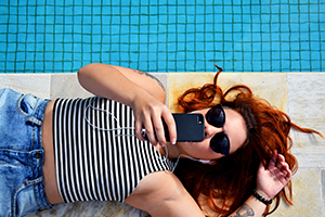 Girl laying poolside on her phone