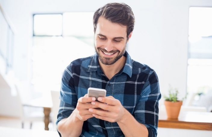 Man smiling at his phone