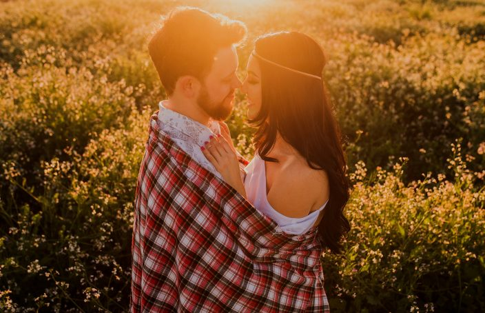 A couple embracing in a field of flowers during a sunset