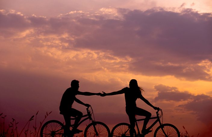 Couple holding hands biking in the sunset