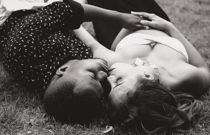 Couple laying in the grass intimately kissing