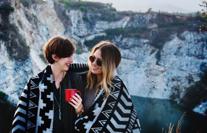 Two women chatting outdoors with blanket wrapped around them.