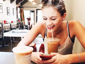 woman using Tinder in a coffeeshop
