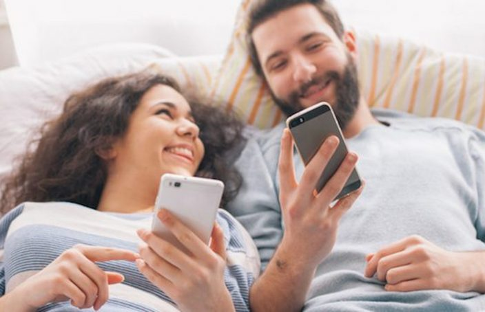 couple on phones in bed